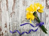stock photo of daffodils  - daffodil flowers with ribbon on a wooden background - JPG