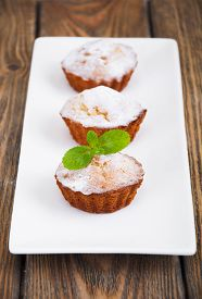 stock photo of bakeshop  - Homemade Muffins Ready for Breakfast on a plate on wooden background - JPG