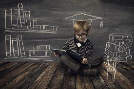foto of child development  - Child Little Boy in Glasses Reading Book over School Black Board with Chalk Drawing Kids Preschool Development Children Education Concept - JPG