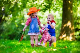 image of cowgirls  - Little boy and girl dressed up as cowboy and cowgirl playing with toy rocking horse in park - JPG