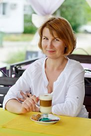 stock photo of ordinary woman  - ordinary woman sitting in cafe with cup of coffee - JPG