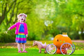 stock photo of carriage horse  - Cute curly little girl playing Cinderella fairy tale holding magic wand next to a pumpkin carriage in autumn park at Halloween - JPG
