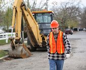 image of road construction  - road construction worker walks determinately toward the camera - JPG