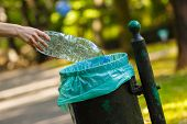 Постер, плакат: Hand Of Woman Throwing Plastic Bottle Into Recycling Bin Littering Of Environmental