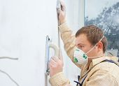 young builder polishing wall poster
