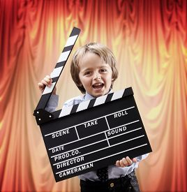 picture of clapper board  - Boy holding a blank clapper board in a cinema theater concept for movie - JPG