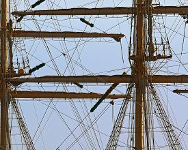 stock photo of sailing vessels  - the mast of a sailing vessel with removed sails against the sky - JPG