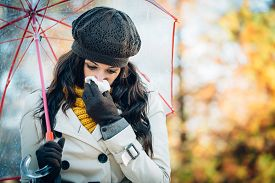 picture of rainy weather  - Sad woman with cold or flu blowing her nose with a tissue under autumn rain - JPG