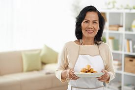 stock photo of eclairs  - Senior Vietnamese housewife with a plate of eclairs - JPG