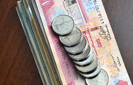 picture of dirham  - Many one dirham coins placed on stack of hundred dirham notes - JPG