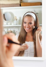 stock photo of face-powder  - Beautiful Woman Applying Powder On Her Face With Brush - JPG