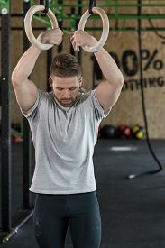 foto of strongman  - Young attractive strongman with gymnastic rings in the gym - JPG