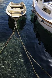 stock photo of school fish  - A moored small boat in a croatian port with a school of small fish visible near the ropes - JPG