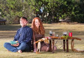 image of sabbatical  - Happy pagan couple at altar with candles and goblets - JPG