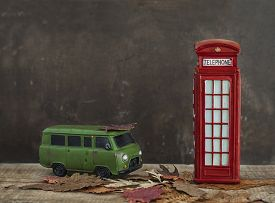 stock photo of phone-booth  - Old green toy van and vintage miniature red phone booth with dry maple leaves on wooden table - JPG