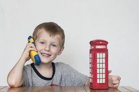 stock photo of phone-booth  - Little cheerful boy talking on the phone and vintage british red telephone booth - JPG