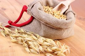 stock photo of oats  - Heap of organic oat grains with wooden spoon in jute bag ears of oat healthy food and nutrition - JPG