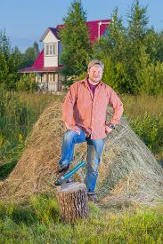 stock photo of haystacks  - Village man have a rest near the haystack - JPG