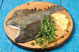 picture of flounder  - Flounder with lemon thyme and pepper on a round cutting board prepared for roasting - JPG