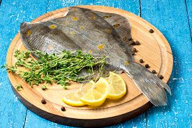 stock photo of flounder  - Fresh flounder with lemon thyme and pepper on a round cutting board and blue wooden table - JPG