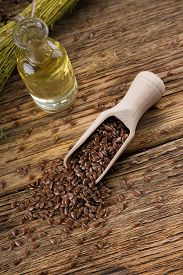 stock photo of flax seed oil  - Vertical photo with heap of flax seeds spilled from wooden spoon on old worn wooden board with glass bottle full of flax oil and with bunch of flax plants bonded by natural cord - JPG