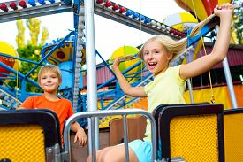 stock photo of carnival ride  - Cute little happy smiling kids riding a Carnival Carousel at summer theme park - JPG