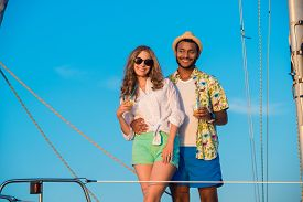 stock photo of yacht  - Loving couple relaxing on a sailing yacht - JPG