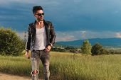 young sexy man walking on the side of a country road near a grass field and looks to side  poster