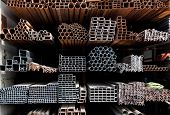 stock photo of ferrous metal  - A series of different sizes metal pipes on  shelf - JPG