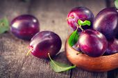 Plum. Healthy juicy ripe organic plums fruit close-up, on wooden table. Prune. Sweet dessert.  poster
