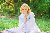 Girl Tender Blonde Sniff Tiny Flower While Sit On Green Grass Meadow. Pure And Tender Concept. Woman poster
