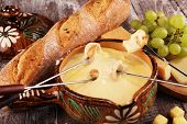 Gourmet Swiss Fondue Dinner On A Winter Evening With Assorted Cheeses On A Board Alongside A Heated poster