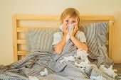 Sick Boy Coughs And Wipes His Nose With Wipes. Sick Child With Fever And Illness In Bed poster