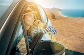 Happiness young woman in hat, sitting in her white car and looking on beautiful ocean coastline with poster