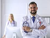 Handsome Smiling Male Doctor. Welcome To Our Clinic. Confident Physician. Office Background. Man Pra poster