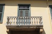 Part Of A Yellow House Wall With An Old Balcony With Shabby  Wooden Columns And A Window With Closed poster