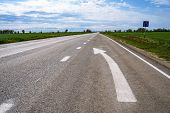 Forward Igns On The Road. White Painting In Turn Left Direction Arrow Symbol On Black Asphalt Road B poster