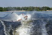 Happy asian man riding water skis on lake in summer and fall down poster