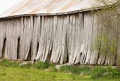 Old Weathered Barn With Lifting Boards And Sloping Roof poster