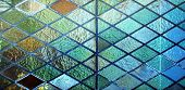 stock photo of stained glass  - A stained multi-coloured glass panel in a diamond design.