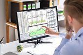 Side View Of Stock Market Broker Looking At Graphs On Screen In Office poster