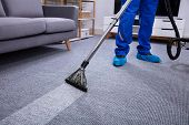 Low Section Of A Male Janitor Cleaning Carpet With Vacuum Cleaning In The Living Room poster