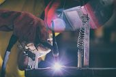 Industrial Worker at the factory or workshop welding steel elements poster