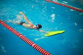 Swimming lessons for kids in sport school, little boy practising swimming in the pool poster