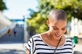 Portrait of happy and young bald woman smiling. Carefree trendy girl with bald head after cancer che poster