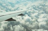 Wing Of Plane Over White Clouds. Airplane Flying On Blue Sky. Scenic View From Airplane Window. Comm poster