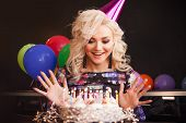 Birthday, A Young Woman Blows Out The Candles On Her Birthday Cake. Birthday Party, Joy And Fun. poster