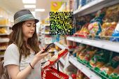 Young Beautiful Woman Chooses Products In The Supermarket And Checks The Qr Code On The Label. The C poster