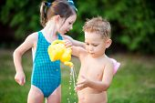 Childhood Summer Games With Water Pool. Caucasian Brother And Sister Play With Plastic Toys Watering poster
