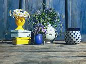 Floral Composition Of Wild Flowers And Old Cans, On Blue Wooden Veranda Background, Outdoor, Morning poster